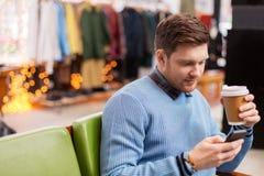 有智能手机和咖啡的人在服装店 库存图片