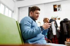 有智能手机和咖啡的人在服装店 免版税库存图片