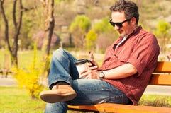 有智能手机和咖啡的人坐长凳 免版税库存照片