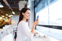 有智能手机和咖啡的微笑的妇女在咖啡馆 免版税库存图片
