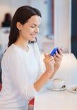 有智能手机和咖啡的微笑的妇女在咖啡馆 库存照片