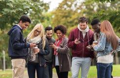 有智能手机和咖啡的愉快的朋友户外 库存照片
