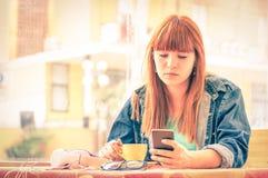 有智能手机和咖啡的沉思少妇 免版税库存照片