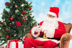 有智能手机和圣诞树的圣诞老人 免版税库存照片