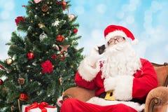 有智能手机和圣诞树的圣诞老人 库存照片