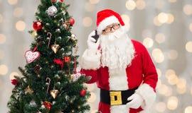 有智能手机和圣诞树的圣诞老人 库存图片
