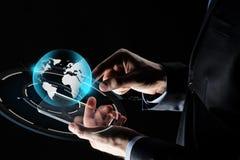 有智能手机和地球的商人手 图库摄影