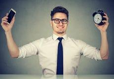 有智能手机和时钟的办公室工作者 免版税库存照片