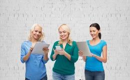 有智能手机和片剂个人计算机计算机的愉快的妇女 免版税图库摄影