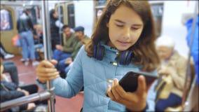 有智能手机和耳机的十几岁的女孩在地铁里面很多人人群地下地铁 ?? 股票视频