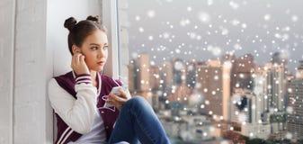 有智能手机和耳机的十几岁的女孩 免版税库存图片