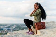 有智能手机和耳机的听到在蓝色多云的音乐的华美的非裔美国人的行家妇女Porrtrait  免版税库存照片