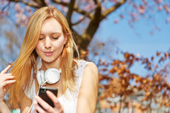 有智能手机和耳机的少年 免版税图库摄影