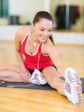 有智能手机和耳机的微笑的女孩在健身房 免版税图库摄影