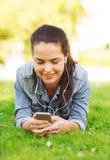 有智能手机和耳机的微笑的女孩 免版税库存照片