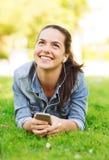 有智能手机和耳机的微笑的女孩 免版税库存图片