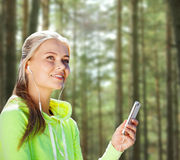 有智能手机和耳机的愉快的妇女 库存照片