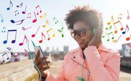 有智能手机和耳机的愉快的少妇 免版税库存照片
