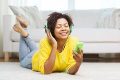 有智能手机和耳机的愉快的非洲妇女 免版税库存照片