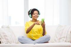 有智能手机和耳机的愉快的非洲妇女 库存图片