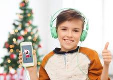 有智能手机和耳机的男孩在圣诞节 免版税图库摄影
