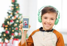 有智能手机和耳机的男孩在圣诞节 免版税库存图片
