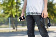 有智能手机和耳机的神奇人在公园的手上 库存照片