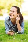 有智能手机和耳机的笑的女孩 免版税图库摄影