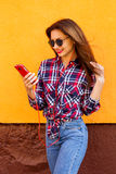 有智能手机和耳机的美丽的时髦的妇女 飞行头发 橙色背景 拷贝空间 免版税库存图片