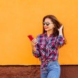 有智能手机和耳机的美丽的时髦的妇女 飞行头发 橙色背景 拷贝空间 库存图片