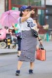 有智能手机和蓝牙耳机的,北京,中国Fashionabel女孩 免版税库存照片