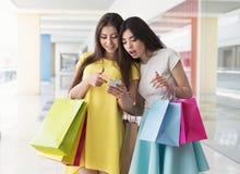 有智能手机和购物袋的惊奇的妇女 免版税图库摄影