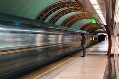 有智能手机射击的孤独的年轻人从在地铁站的外形与模糊的移动的火车在背景中 库存图片