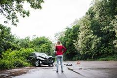 有智能手机的一个少妇乘在车祸以后的损坏的汽车,打电话 免版税图库摄影