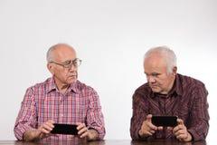 有智能手机的两个人 免版税库存照片
