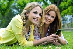 有智能手机的两个姐妹在公园 库存照片