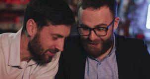有智能手机的两个老朋友谈话在啤酒客栈在晚上 股票视频