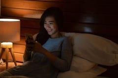 有智能手机的亚裔妇女,当放置在床时 库存照片