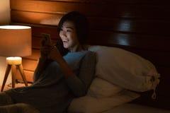 有智能手机的亚裔妇女,当放置在床时 免版税图库摄影