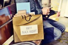 有智能手机的人和与文本愉快的黑星期五的一个袋子 免版税图库摄影