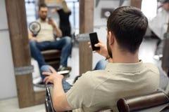 有智能手机的人在理发店或美发店 库存照片