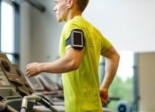 有智能手机的人行使在健身房的踏车的 免版税库存图片