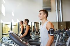 有智能手机的人行使在健身房的踏车的 免版税库存照片