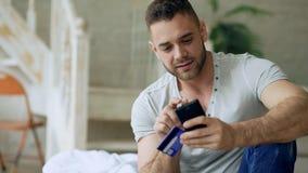 有智能手机的可爱的年轻人和在互联网上的信用卡购物在家坐床 免版税图库摄影