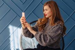 有智能手机的可爱的时髦的少女做selfie在水色背景 库存照片