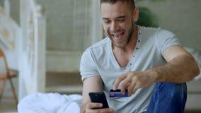 有智能手机的可爱的年轻人和在互联网上的信用卡购物在家坐床 股票录像