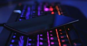 有智能手机的喂结束多色的被带领的键盘对此摇摄在黑暗的环境里 股票视频