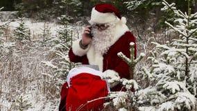 有智能手机的圣诞老人在礼物袋子附近在多雪的森林 股票视频