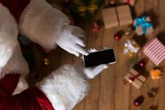 有智能手机的圣诞老人 库存图片