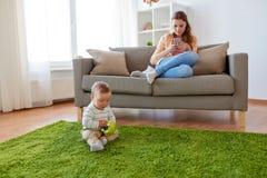 有智能手机的在家使用母亲和的婴孩 库存照片